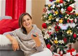 Happy woman watching TV near Christmas tree