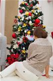 Woman sitting near Christmas tree. Rear view