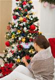 Woman sitting near and decorating Christmas tree. Rear view