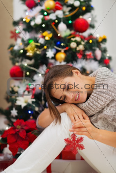 Calm woman near Christmas tree and playing with Christmas toy