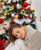 Calm woman sitting near Christmas tree