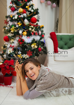 Happy woman laying near Christmas tree