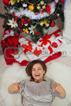 Happy woman laying near Christmas tree and pointing in camera