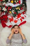 Happy woman laying near Christmas tree and shouting through megaphone shaped hands