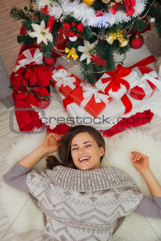 Happy woman laying near Christmas tree. Upper view
