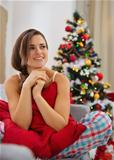 Happy woman sitting on divan in front of Christmas tree