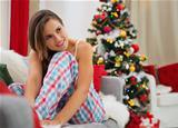 Dreaming woman sitting on sofa in front of Christmas tree