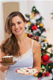 Happy woman in pajamas holding hot beverage and cookies in front of Christmas tree