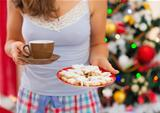 Closeup on woman in pajamas holding hot tea and cookies in front of Christmas tree