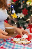 Closeup on woman in pajamas holding hot chocolate and cookies in front of Christmas tree