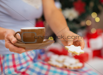 Closeup on woman in pajamas holding hot beverage and cookies in front of Christmas tree