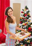 Happy woman in pajamas holding bed table with snacks in front of Christmas tree