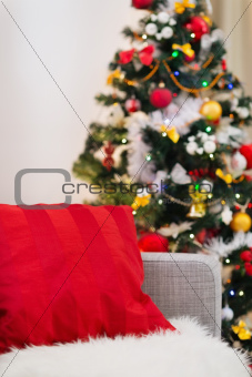 Closeup on sofa with red pillow in front of Christmas tree