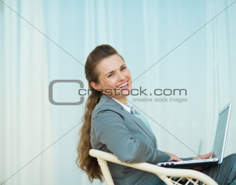 Happy business woman sitting with laptop