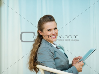 Happy business woman sitting with tablet PC