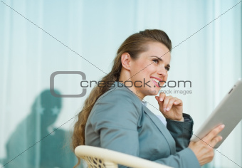 Thoughtful business woman using tablet PC