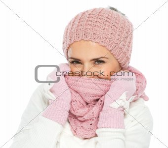 Woman in knit winter clothing closing face with knit scarf