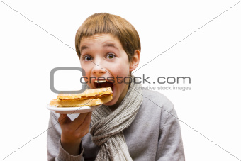 Portrait of a cute boy eating a waffle - isolated on white