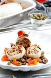 baked sepia with tomatoes and black olives filled with pearl barley risotto