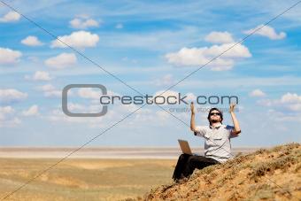 man with laptop praying to the God