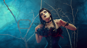 Pretty gothic girl wearing tight feather corset