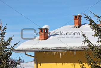 Red chimneys on snowy roof. Piedmont, Italy.