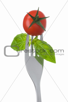 tomato and basil on a fork on white