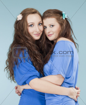 two young female friends hugging, looking - isolated on blue