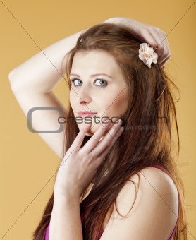 portrait of a young beautiful woman with brown hair - isolated on yellow