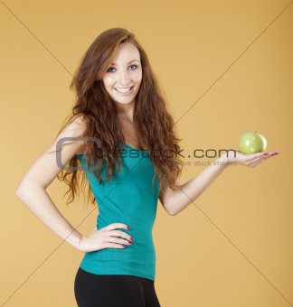young girl holding a green apple smiling - isolated on yellow