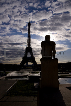 Backlit Eiffel Tower with statue