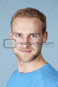 portrait of a young man with blond hair - isolated on blue