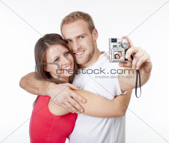 happy young couple taking pictures of themselves - isolated on white