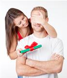 young woman covering her boyfriends eyes to give him a surprise present