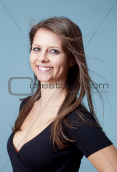 portrait of a young beautiful woman with brown hair - isolated on blue