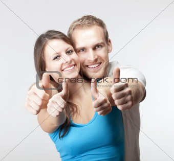 young couple showing both thumbs up smiling- isolated on gray