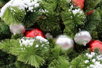 Colorful ornaments tucked into green pine boughs.