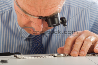Man with Magnifying Glasses Fixing Watch