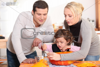 Parents carving a pumpkin with their daughter
