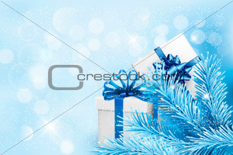 Holiday blue background with gift boxes and tree branches. Vector illustration.