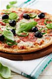 Pizza with salami, chili pepper and olives