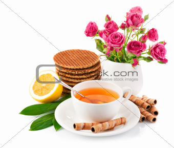 tea in cup with biscuits and lemon
