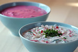 Chl'odnik - cold beetroot soup in a bowl on a wooden table.