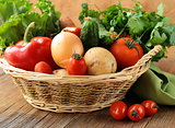 fresh vegetables and herbs mix in a wicker basket