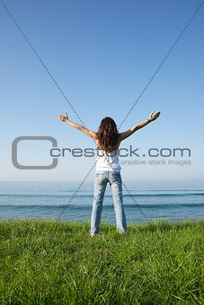 cross woman at grass seashore