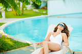 Young woman in swimsuit relaxing poolside
