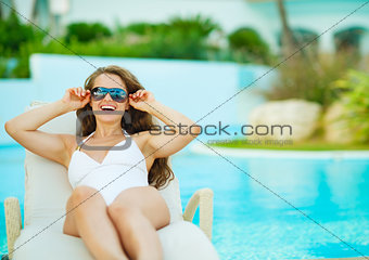 Happy young woman in swimsuit relaxing on chaise-longue