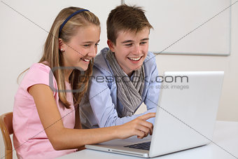 Two young students working on a laptop