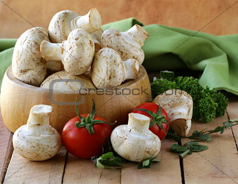 Fresh champignon mushrooms on a wooden table