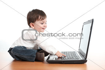 Casual baby smiling while is playing with a laptop computer